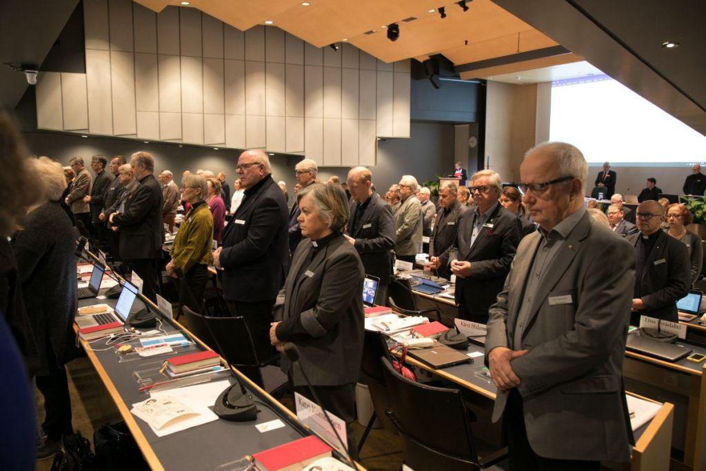 Kirkolliskokousedustajat seisovat paikoillaan istuntosalissa hiljentyneinä aamurukoukseen.