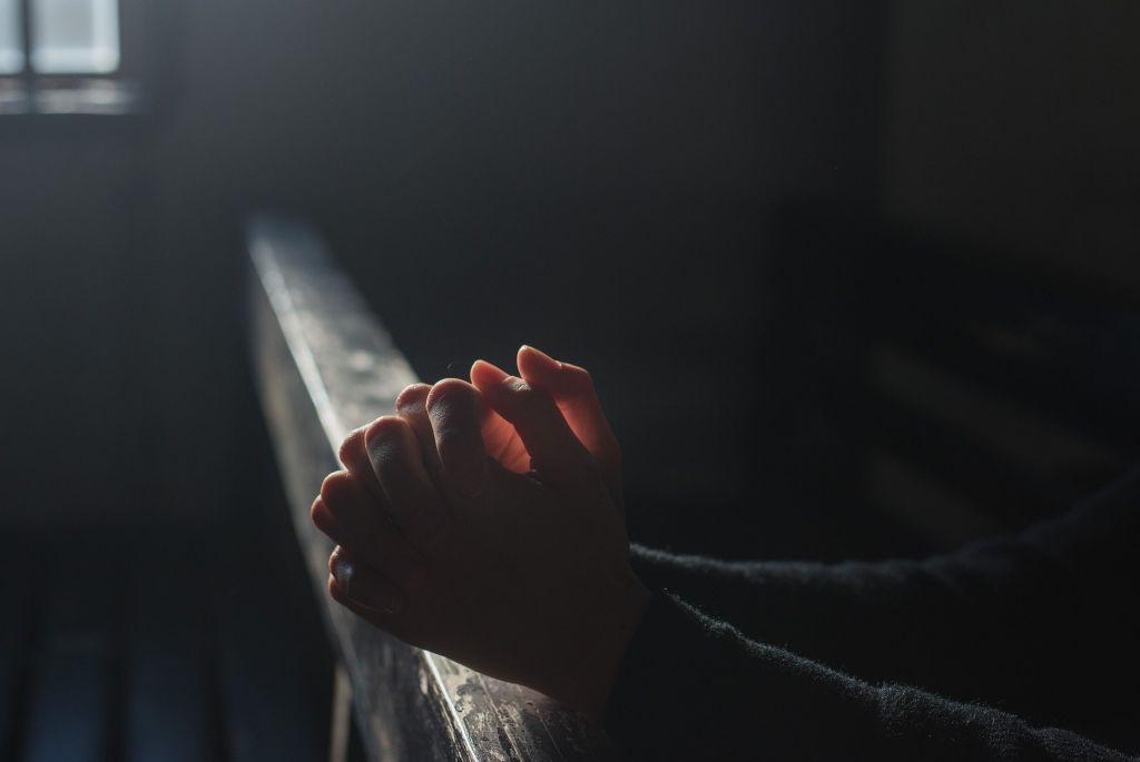 Lähikuva rukoukseen liitetyistä käsistä hämärässä kirkonpenkissä.