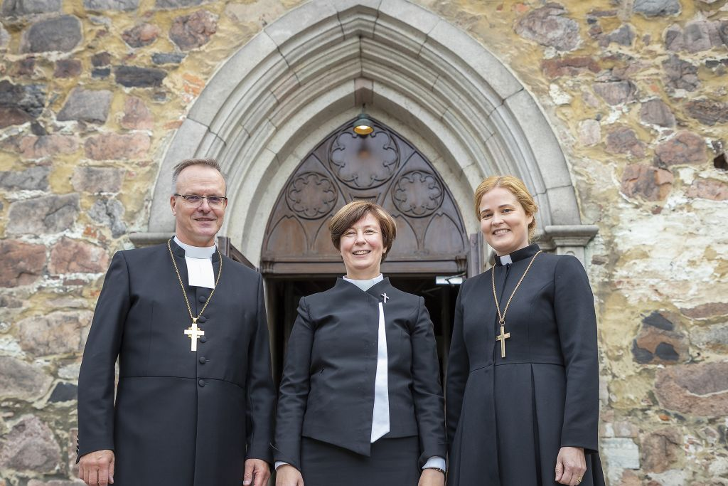 Kolme piispaa kirkon portailla.